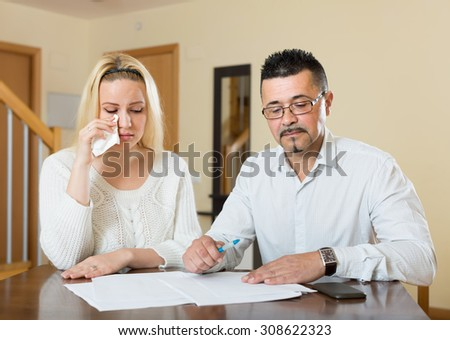Couple having conflict over financial documents at home. Focus on man - stock photo