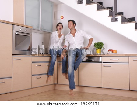 Couple having fun in the kitchen at home by throwing a apple - stock photo