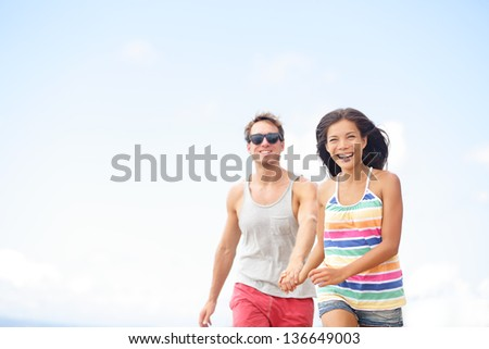 Couple having fun laughing in love outside running together holding hands. Joyful happy happiness lifestyle image with interracial young couple in their twenties, Asian woman, Caucasian man. - stock photo