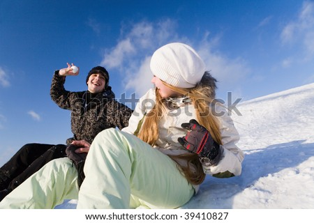Couple having fun on snowboards at winter day - stock photo