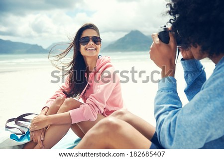 Couple having fun taking photos with retro vintage hipster camera at beach - stock photo