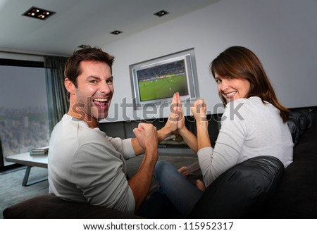 Couple having fun watching soccer game - stock photo