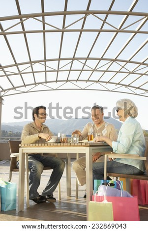 Couple Having Lunch Outdoors with Young Man - stock photo