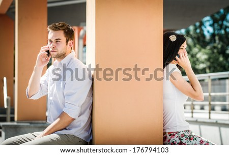 Couple having problems - two people sitting on opposite side of big collumn calling phone - stock photo