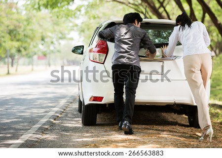 Couple helped us push the car. Was broken on the side - stock photo