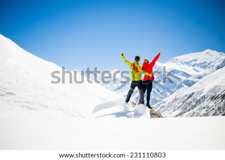 Couple hikers man and woman success in winter mountains. Inspiration and motivation in beautiful landscape. Fitness healthy lifestyle outdoors on snow in Himalayas, Nepal. Annapurna range trekking sky - stock photo