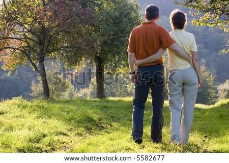 Couple hiking at sunset in fall - stock photo