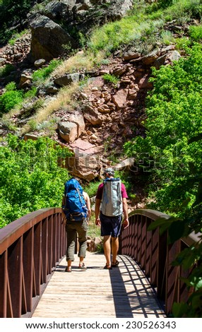 couple hiking over a bridge in the Colorado wilderness  - stock photo