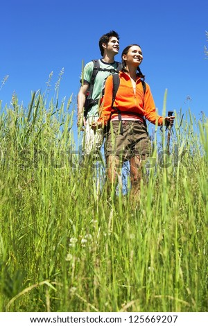 couple hiking together, blades of grass in the foreground, both wearing backpacks and holding hiking stick - stock photo