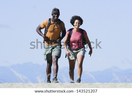 Couple hiking together in mountains - stock photo