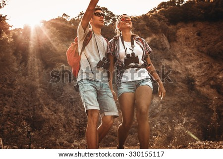 Couple hiking. Using map to get good direction.Grain effect adder for artistic impression. - stock photo