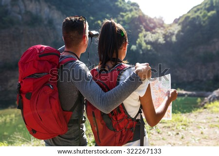Couple hiking. Using map to get good direction.View from behind. - stock photo