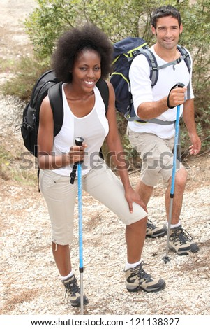 Couple hiking with sticks - stock photo
