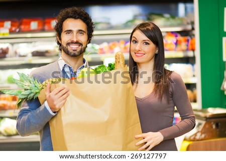 Couple holding a bag full of vegetables at supermarket - stock photo