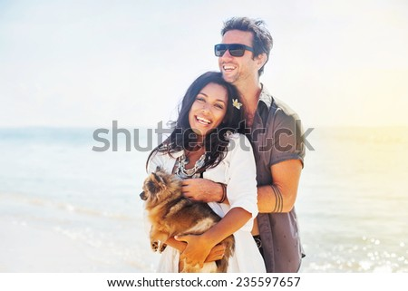 couple holding a puppy on a beach - stock photo