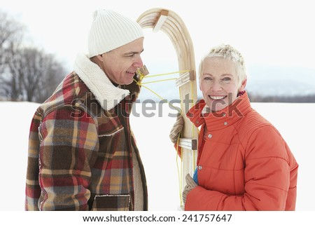 Couple holding a sled - stock photo