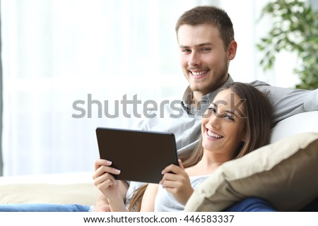 Couple holding a tablet posing sitting on a couch at home and looking at camera - stock photo
