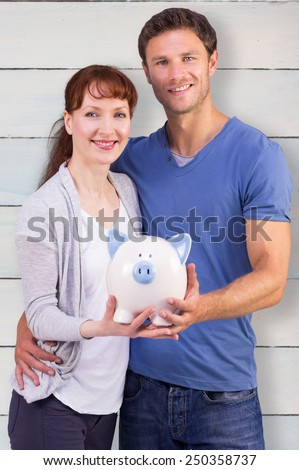 Couple holding a white piggy bank against wooden planks - stock photo