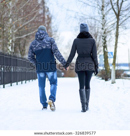 Couple holding each other's hands, the winter goes on the road, enjoying a stroll, a love couple. Husband and wife are going through the park holding hands in the winter. The movement of people. - stock photo