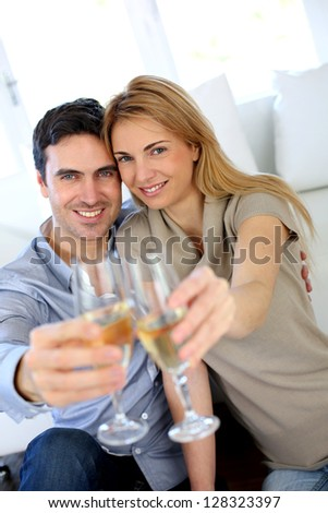 Couple holding glass of champagne towards camera - stock photo