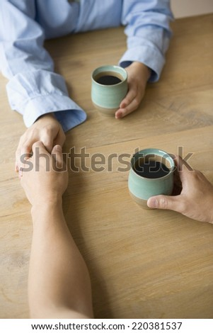 Couple holding hands across the table - stock photo