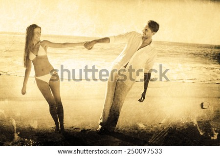 Couple holding hands and leaning to either side against grey background - stock photo