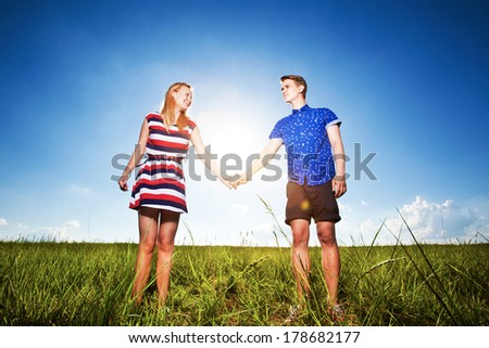 Couple holding hands and walking in green field - stock photo