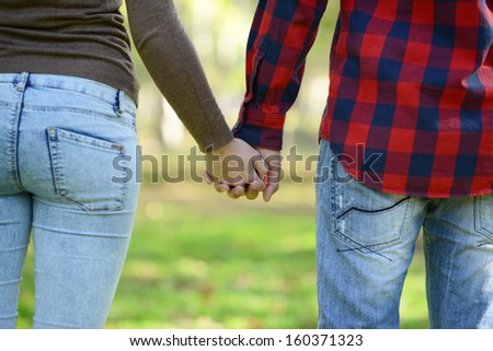 Couple holding hands and walking in park - stock photo