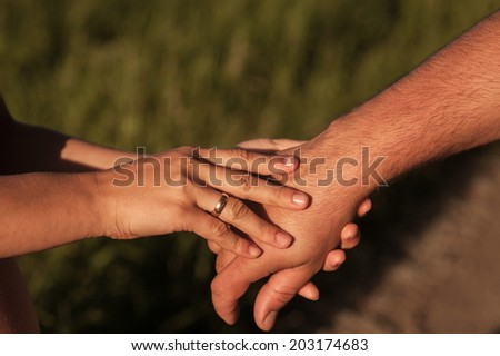 Couple holding hands at sunset - stock photo