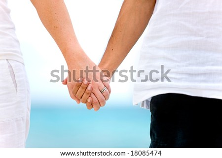 couple holding hands by the sea in a romantic setting - stock photo
