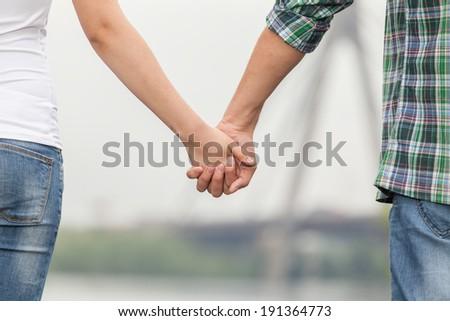 Couple holding hands. Couple holding hands while walking along quay - stock photo