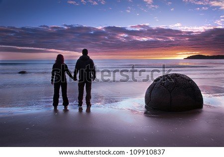 Couple holding hands looking at the sunrise at Moeraki Boulders - stock photo
