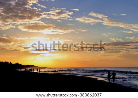 Couple holding hands on sunset beach walk - stock photo