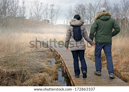 couple holding hands walking along boardwalk on misty morning                    - stock photo