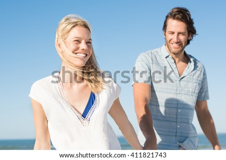 Couple holding hands walking away on the beach. Cheerful couple walking on a sandy beach. Couple having fun laughing in love at sea shore. 