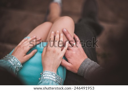 couple holding hands while sitting together no face  - stock photo