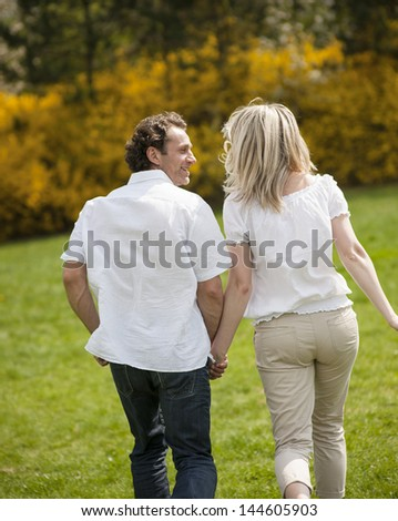 Couple holding hands with back to camera running through park - stock photo