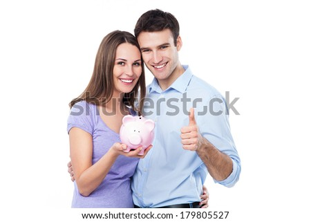 Couple holding piggy bank and showing thumbs up - stock photo