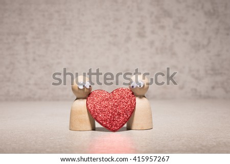Couple holding red heart. Wooden figures with cute and funny symbol of love. Concept of romantic feelings, dating insecurity and valentine celebration. - stock photo