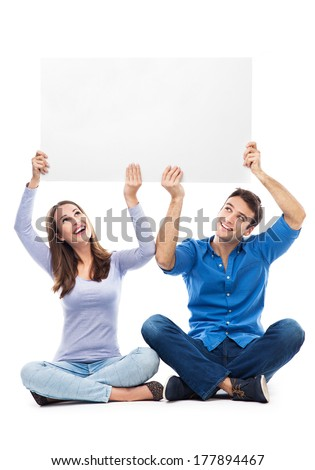Couple holding sign above their heads  - stock photo
