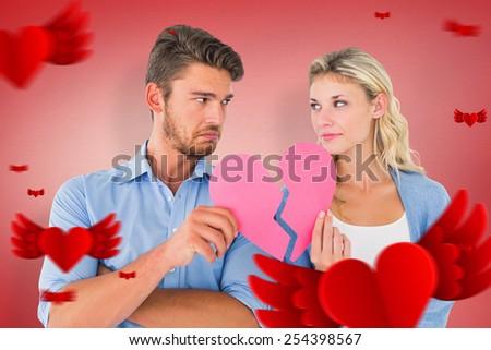 Couple holding two halves of broken heart against red vignette - stock photo