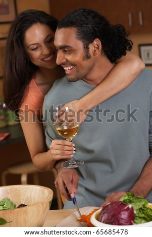 Couple hugging and drinking while cooking - stock photo