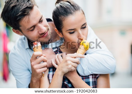 Couple hugging and eating ice cream on street - stock photo