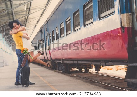 Couple hugging at the train station, girl is jumping - stock photo