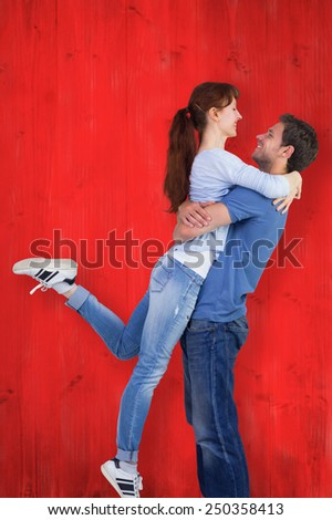 Couple hugging each other against red wooden planks - stock photo