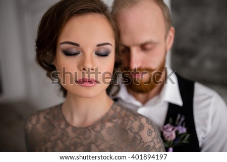 couple hugging in a white room with a fireplace and candles, the bride wearing a gray dress with a lace, the groom with a red beard in black trousers, white shirt and black vest, close-up portrait - stock photo