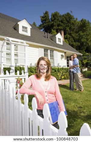 Couple hugging in front of house with real estate agent - stock photo