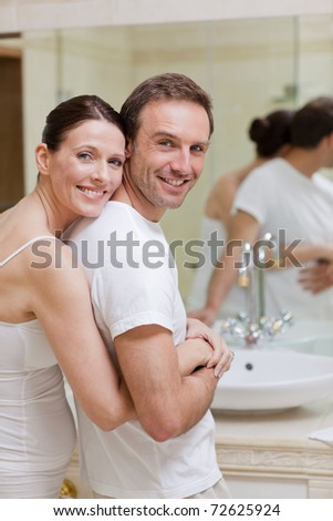 Couple hugging in the bathroom - stock photo