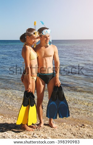 Couple hugging on the beach before snorkeling in the Black Sea. They are in love. Active couple on summer vacation. Couple has modern protective workwear: mask, tube and flipper.  - stock photo