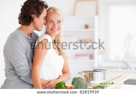 Couple hugging while cooking in their kitchen - stock photo